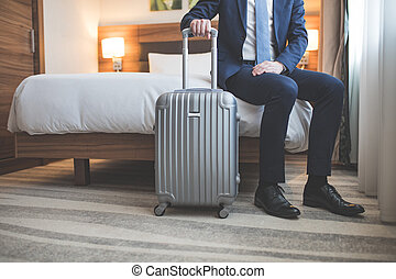 Young businessman with a suitcase in room
