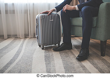 Young businessman with a suitcase indoors