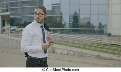 Young businessman with glasses and ponytail in suit holding...