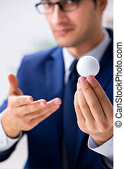 Young businessman with golf ball working in office