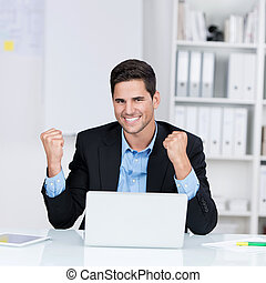 Young Businessman With Laptop Celebrating Victory At Desk