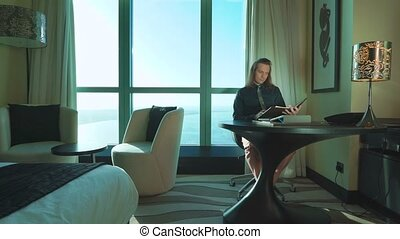 Young businessman with long hair is working on tablet, types...