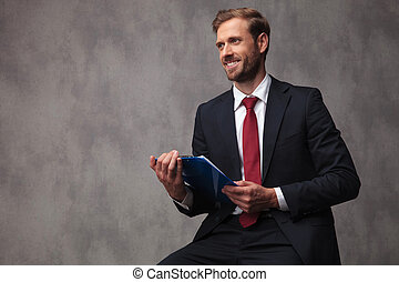 young businessman with notepad looks to side and smiles