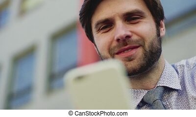 Young businessman with smartphone sitting outside in city, texting. Close up.