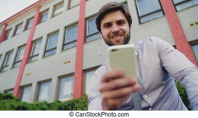 Young businessman with smartphone sitting outside in city, texting.