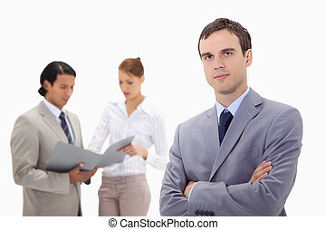 Young businessman with talking colleagues behind him
