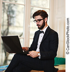 Young businessman working at a laptop in the office opposite the window