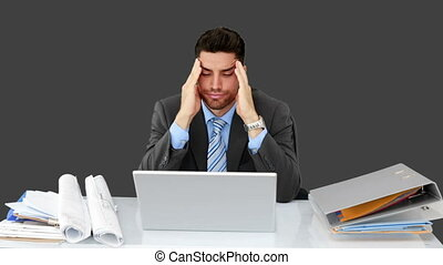 Young businessman working at his desk on grey screen background