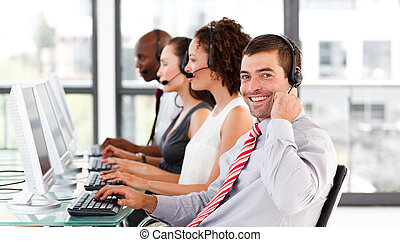 Young businessman working in a call center with his colleagues smiling at the camera