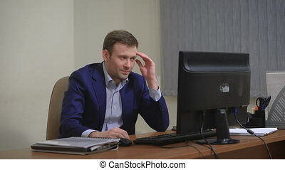 Young businessman working in office, sitting at desk, looking at computer screen.