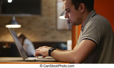 Young businessman working on computer in cafe. 4k.