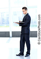 Young businessman working on laptop, standing in office