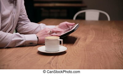 Young businessman working on tablet  in cafe
