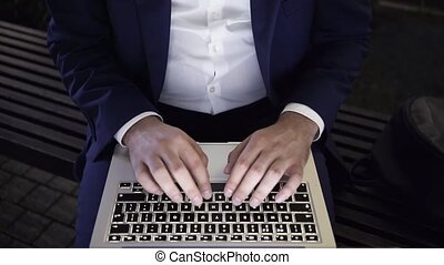 Young businessman working with a laptop on a bench at night top view