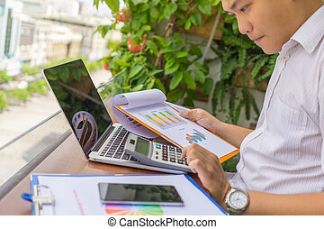 Young businessman working with calculator and financial reports