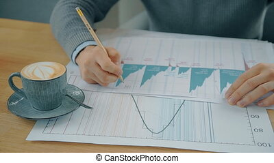 Young businessman working with financial project, sitting at table in coffee shop.