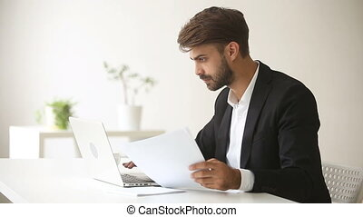 Young businessman working with laptop documents, using business accounting application