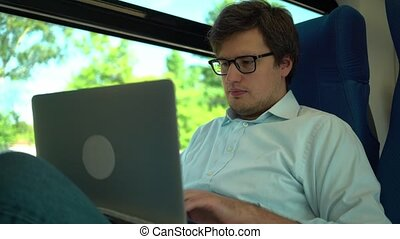 Young businessman working with laptop on train and smiling