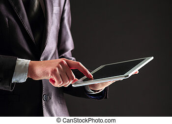 Young businessman working with modern devices, digital tablet PC on a black background