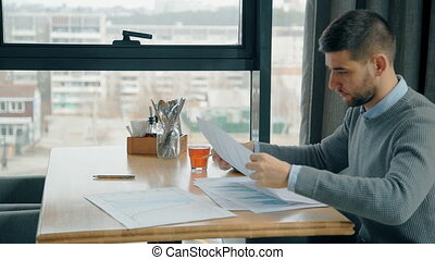 Young businessman working with start up project, sitting at table in cafe.