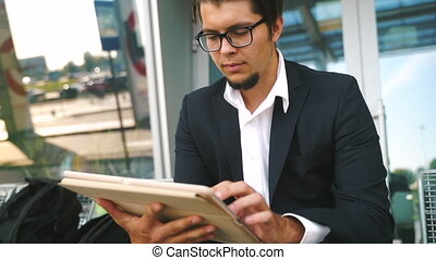 Young businessman works with tablet, checks mail, surfing the Internet, prepares a presentation