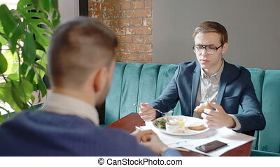 Young businessmen are talking during business lunch, sitting at table in restaurant.