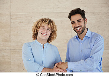 Young businessmen shaking hands smiling