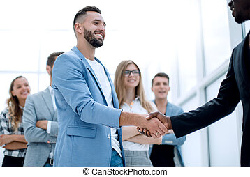 young businessmens shaking hands in the office