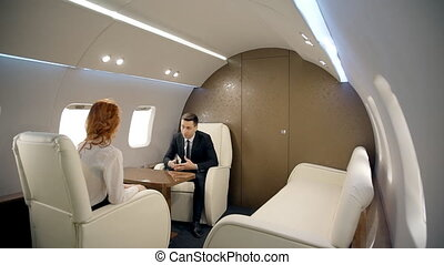 Young businesspeople are discussing modern business, sitting in private plane.