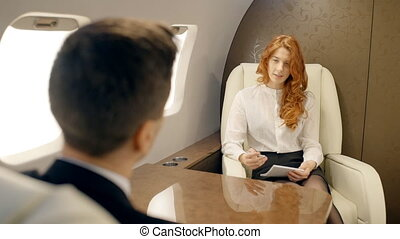 Young businesspeople are discussing project sitting at table in airplane interior.