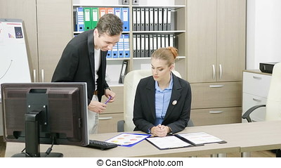 Young Businesspeople at a desk office talking and analyzing...