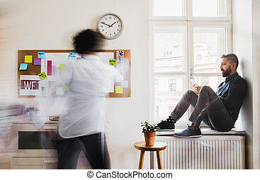 Young businesspeople in a modern office, having break. Motion blur.