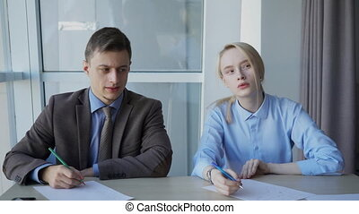 Young businesspeople is talking while sitting at desk in modern office.