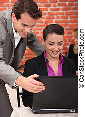 Young businesspeople looking at a laptop