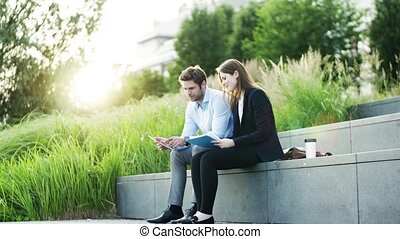Young businesspeople with tablet sitting outdoors at sunset, making notes.
