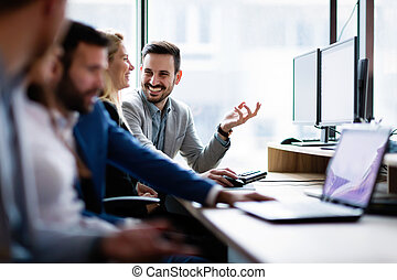 Young businesspeople working on computer in office - Young ...