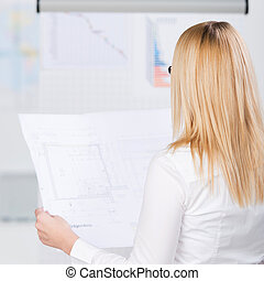Young Businesswoman Analyzing Blueprint