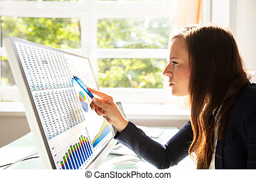 Businesswoman Analyzing Graphs On Computer