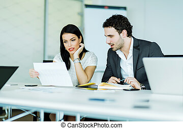Young businesswoman and a businessman looking at a paper while sitting at a office desk
