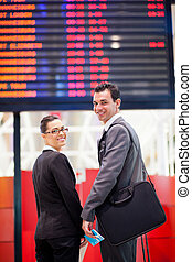 businesswoman and businessman in front of airport information board