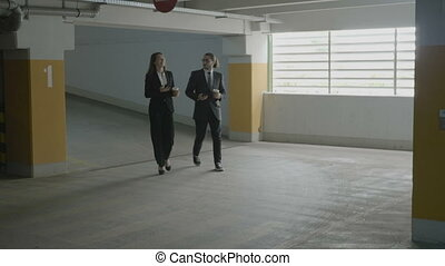 Young businesswoman and businessman walking in a parking lot to their car and discussing about work while holding coffee and phones in their hands
