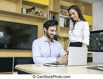 Young businesswoman and businessman working in modern office
