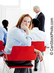 Young businesswoman bored at a conference with her...