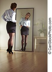 Young businesswoman checking herself in the mirror....