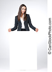 Young businesswoman cover her lag with blank poster. Smiling and looking at the camera