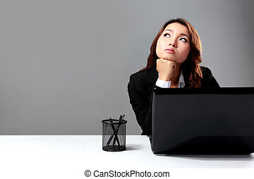 Young businesswoman daydreaming in front of a laptop - A...