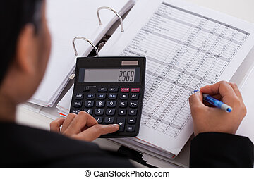 Businesswoman Doing Calculations - Young Businesswoman Doing...