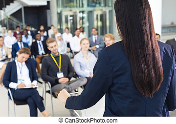 Young businesswoman doing speech in conference room