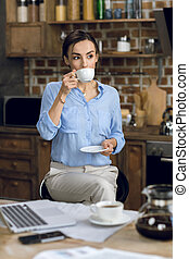 young businesswoman drinking coffee at morning
