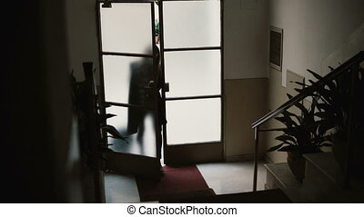 Young businesswoman entering to the apartment with suitcase. Female opens the door and going up on stairs.